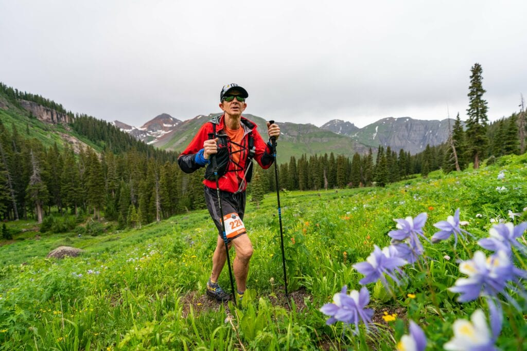 older guy climbing with columbines in foreground-min