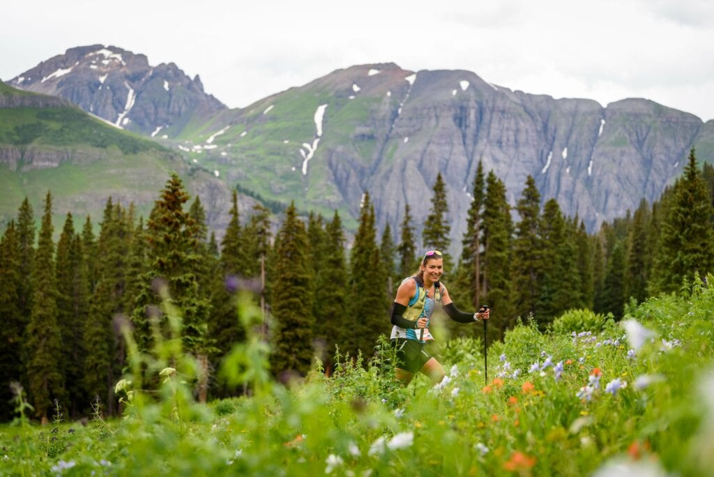 woman climbing slope with wildflowers and big mountain in background-min