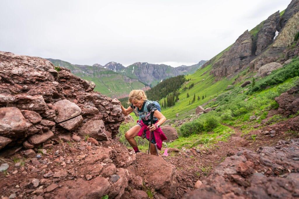 woman climbing up rocks with mountain backdrop-min