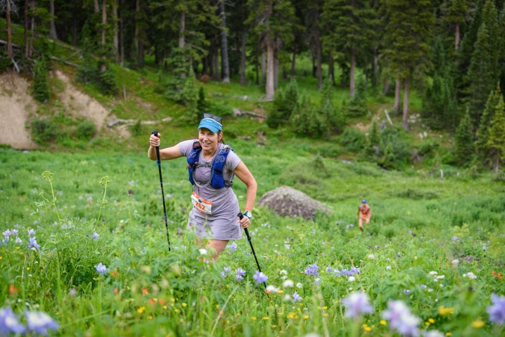 woman climbing wildflower slope with poles and big smile-min